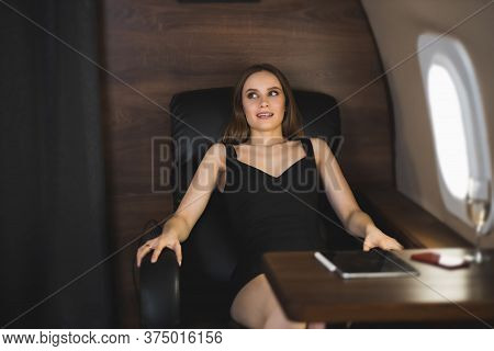 Scared Girl In Black Dress With Fear Of Flight Sitting In Seat In Private Plane. Concept Of Aerophob