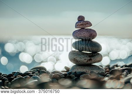 Balanced Pebbles Pyramid On The Beach On Sunny Day And Clear Sky At Sunset. Blue Sea On Background.