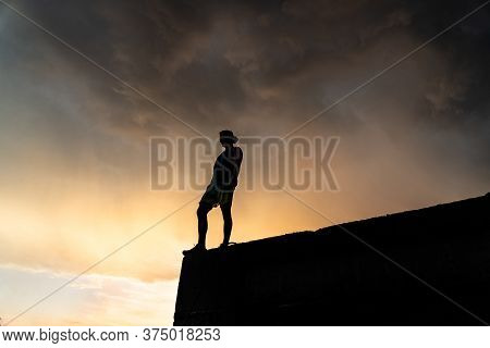 Man On The Edge Of Cliff Standing Over Dramatic Sky During Sunset .concept Of Thinking, Meditation A