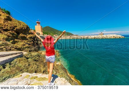 Happy Woman In Rio Marina Beach On Top With Red Hat. Caucasian Tourist On Holiday Travel In Italy. R