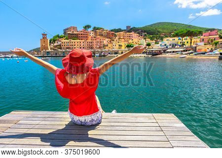 Happy Woman Sitting Over Jetty And Looking At Rio Marina Harbor Of Elba Island In Red Suit. Lifestyl