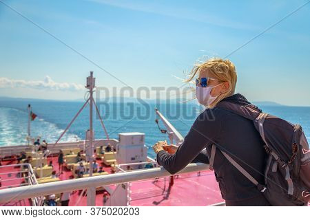 Woman On Ferry Boat With A Surgical Mask During Covid-19 Looking Tuscany Panorama. Tourist Travels O