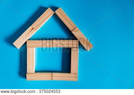 Wooden House On A Blue Background. Lending To The Public. The Concept Of Affordable Housing And Mort