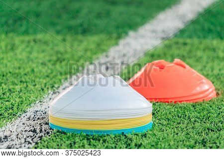 Stacks Of Sport Marker Cone On Training Pitch With Green Field And White Boundry Line.