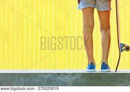 Young Skateboarder Girl In Skate Park. Close Up View Of Legs, Sneakers, Skateboard. Active Family Li
