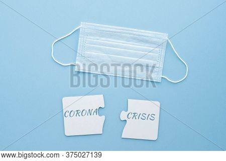 Two White Puzzles With The Separated Word Corona Crisis, Medical Mask On A Blue Background, Crisis 2