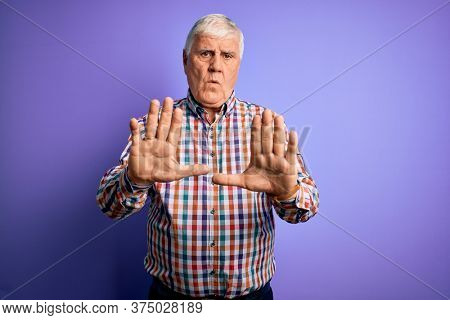 Senior handsome hoary man wearing casual colorful shirt over isolated purple background Moving away hands palms showing refusal and denial with afraid and disgusting expression. Stop and forbidden.