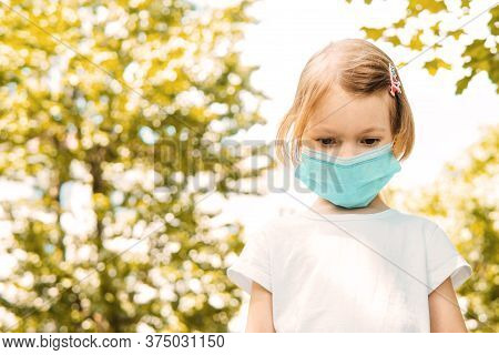 Little Cute Girl In Face Mask Looking Down, In The Outdoor, Trees On Background, Close Up. Concept O