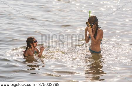 Children With Underwater Pipes In Sea. Children With Masks Floating In Water. Scuba Diving. Looking