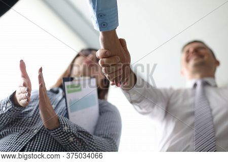 Low Angel Photo Of Happy Adult Businessmen Making Handshake With His Partner With Woman Next To Him.