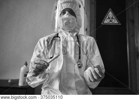 Black And White Snapshot Of Medical Worker Holding Covid-19 Swab Collection Kit, Wearing White Ppe P