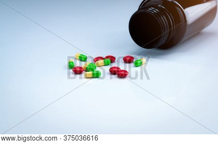 Green And Yellow Capsules With Red Tablets Pills Near Brown Drug Bottle On White Background. Pharmac
