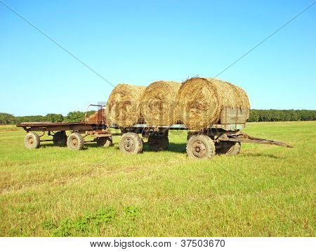 Three Rolls Of Hay On A Cart