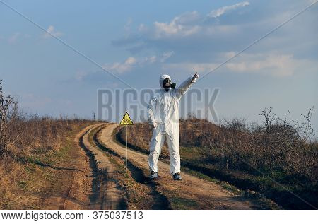 Environmentalist Standing On The Road Near Yellow Triangle With Skull And Crossbones Warning Sign An