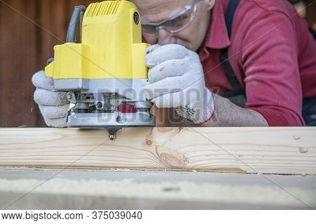 Craftsman Works On Wooden Workpiece With Milling Tool At Cottage Workshop. Processing Of Natural Woo