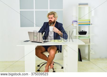 Man Is Working At Home During Coronavirus Pandemic. Relaxed Man Sit On Comfortable Chair Using Lapto