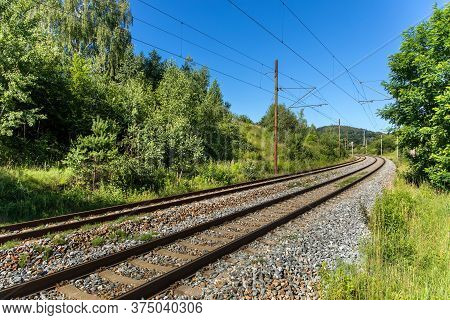 Railroad Ties And Track Surrounded By Shrubbery At A Curve In Czech Republic. Close-up Of A Slightly
