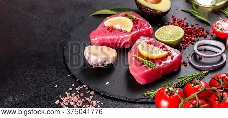Fresh Tuna Fillet Steaks With Spices And Herbs On A Black Background