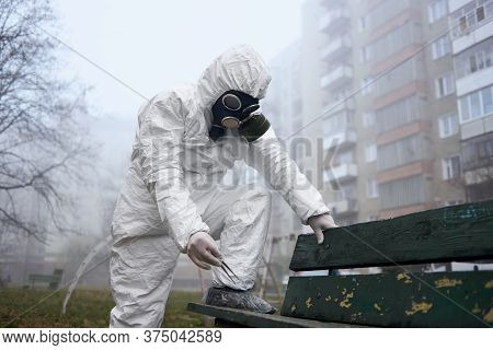 Research Scientist Holding Tweezers While Standing By Bench. Male Environmentalist Wearing Protectiv