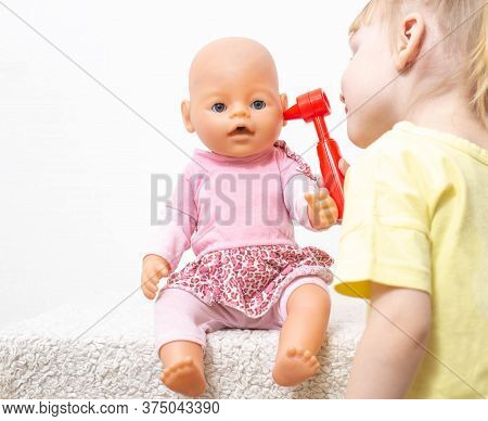 Little Girl Inspects The Ears Of Her Doll On A White Background. The Concept Of Pediatric Otolaryngo