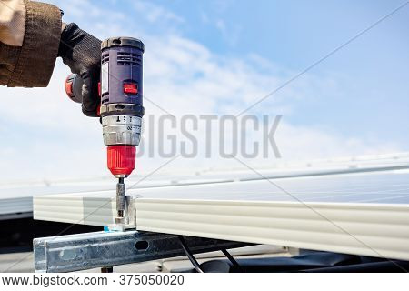 Solar Engineer Male Hand Working With Drill Installing Solar Panel On House Roof Against Blue Sky. S