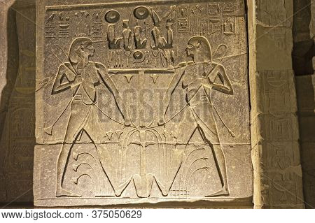 Large Hieroglyphic Carvings On Wall At Ancient Egyptian Luxor Temple Lit Up During Night Background