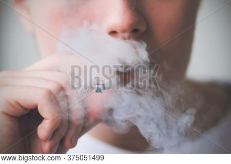 A Young Guy In A White T-shirt Takes A Drag From A Cigarette And Exhales Thick Toxic Harmful Smoke.
