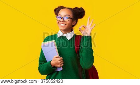 Everything Is Okay. Smiling Black Teenage Girl Showing Ok Sign, Looking At Camera Over Yellow Wall,