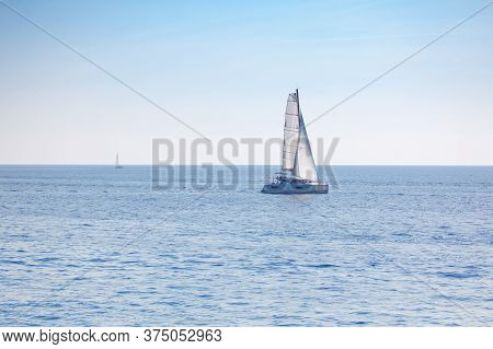 Sailing Yacht With Long Masts And White Sails . Modern Boat In Open Sea
