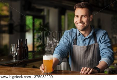 Lager, Ale And Beer. Handsome Fashionable Barman In Apron Puts Glass With Light Drink On Wooden Bar