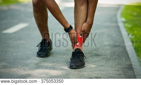 Unrecognizable Young Jogger Feeling Pain In His Ankle During His Morning Run At Park, Close Up. Pano