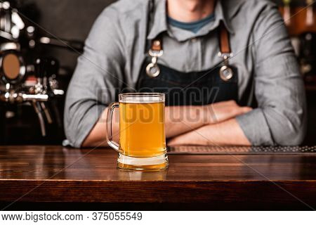 Welcome To Bar. Barman In Apron With Crossed Arms At Bar And Meets Client With Glass Of Light Beer I