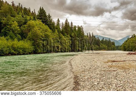 Upper Kitimat, Glacial Green River, On A Cloudy Summer Day, With Rainforests And Gravel Bars, In Bri