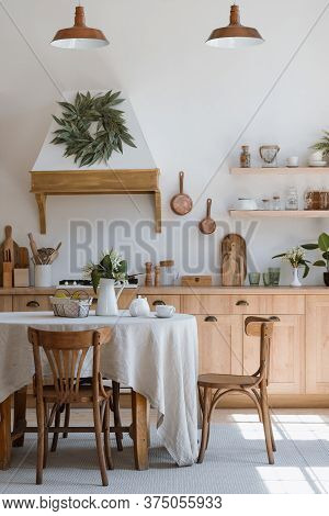 Vertical Photo Of Comfortable Kitchen Room With Tablecloth, Fruits And Flowers On Dinner Table. Mode