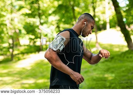 Side View Of African American Jogger Checking His Smartwatch Or Fitness Tracker During Morning Run A