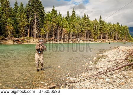 Kitimat, British Columbia, Canada - July 27th, 2015: A Sport Fly Fisherman Hooked Into A Salmon On T