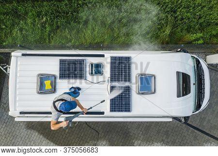 Caucasian Men In His 40s Power Pressure Washing Recreational Vehicle Rv Camper Van Roof Equipped Wit