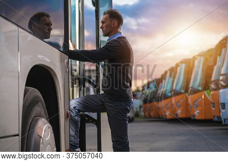 Caucasian Male Passenger In His 40s Getting Into Public Shuttle Bus On The Bus Station. Many Coaches