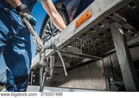 Caucasian Worker Securing Car On Towing Truck Using Tie Down Belts. Transportation And Cargo Theme.