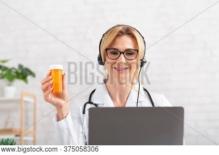 Advertisement Of Medicaments. Smiling Woman Doctor In Headphones Hold Jar In Hand, Sitting At Table