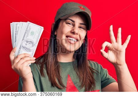 Woman wearing t-shirt with red star communist symbol holding bunch of dollars banknotes doing ok sign with fingers, smiling friendly gesturing excellent symbol