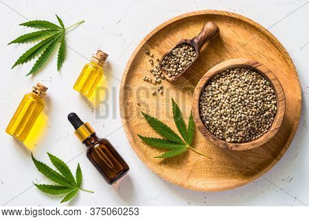 Cannabis Oil Hemp Oil With Cannabis Seeds And Cannabis Leaves At White Table. Top View With Copy Spa