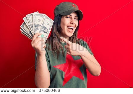 Woman wearing t-shirt with red star communist symbol holding bunch of dollars banknotes smiling happy pointing with hand and finger
