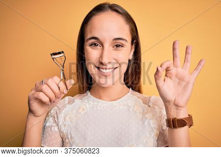 Young beautiful woman using eyelash curler standing over isolated yellow background doing ok sign with fingers, excellent symbol