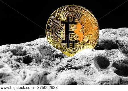Golden Bitcoin Coin On Grey Rock . Bitcoin Cryptocurrency. Business Concept.