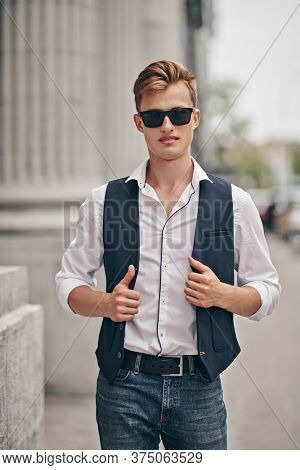 Handsome young man walking along the city promenade. Summer fashion. Summer holidays and vacation.