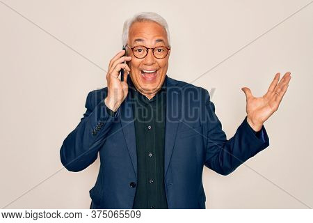Middle age senior grey-haired business man wearing glasses talking on smartphone very happy and excited, winner expression celebrating victory screaming with big smile and raised hands