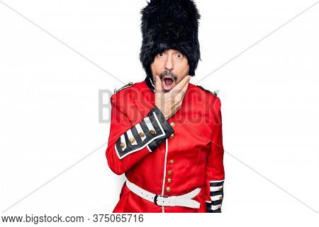 Middle age handsome wales guard man wearing traditional uniform over white background Looking fascinated with disbelief, surprise and amazed expression with hands on chin