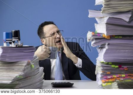 Tired Office Worker Yawns Tired Sitting At Desk With Huge Pile Of Documents. Fatigue And Overload Co
