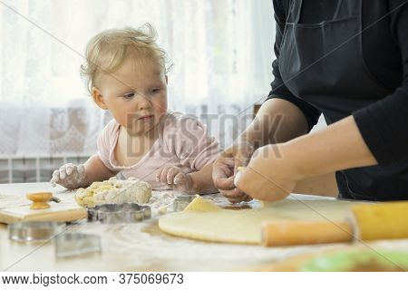 Close Up View Of Little Cute Baby And Grandma In Apron Cooking On Kitchen, Make Homemade Pastry. Gra